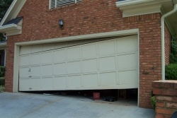 "alt= ""A garage door that is off the door track on the right side being fixed by the experts at five-star doors located in Farmington Mi."""