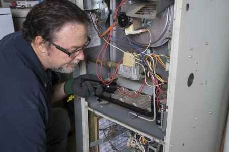 "alt=""HVAC Technician working on a gas furnace for a customer in South Lyon who works for TNT Heating and Cooling."""